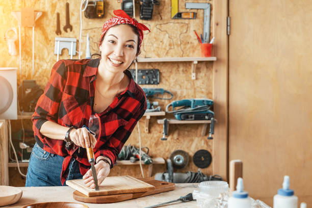 Asian Woman craftsman creates wood products for sale in her shop. Handmade and design concept stock photo