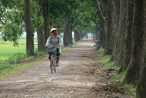 Asian woman cycling on a country road