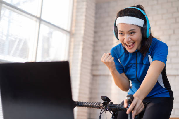 Asian woman cyclist. She is exercising in the house. By cycling on the trainer And playing online bike games, she is satisfied stock photo