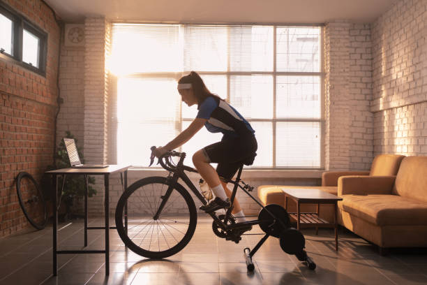 Asian woman cyclist. She is exercising in the house.By cycling on the trainer and play online bike games stock photo