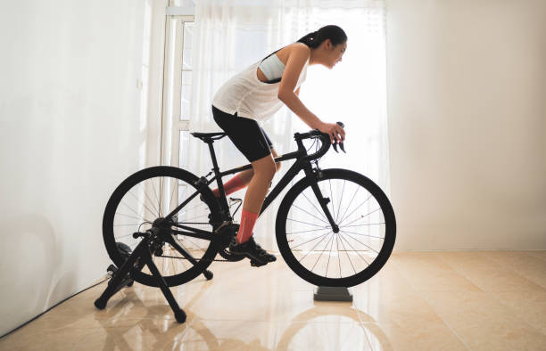 Asian woman cyclist. She is exercising in the house.By cycling on the trainer stock photo