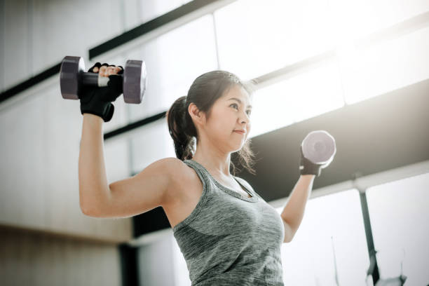 Asian woman doing exercise with dumbbell at gym stock photo