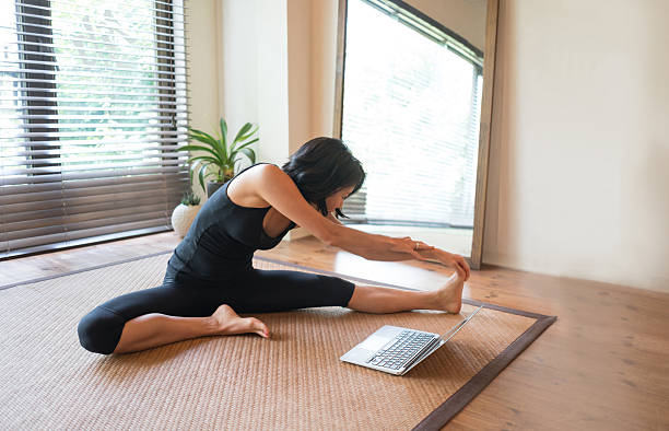 asian woman doing yoga at home - yoga videos online stock-fotos und bilder
