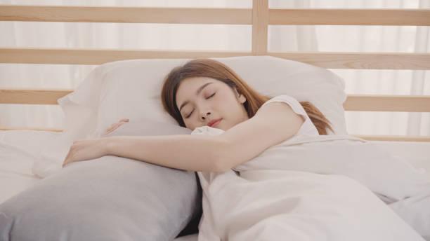 Asiatische Frau träumt beim Schlafen im Schlafzimmer im Bett, wunderschönes japanisches Weibchen, das sich zu Hause auf dem Bett befindet. Lifestyle-Frauen, die sich entspannt zu Hause fühlen. – Foto