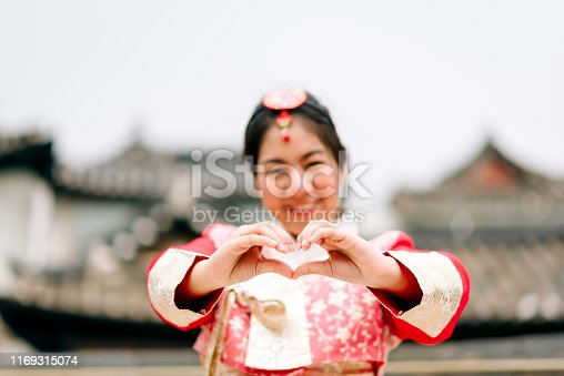 Asian woman dressed Hanbok showing heart sign in Seoul, South Korea