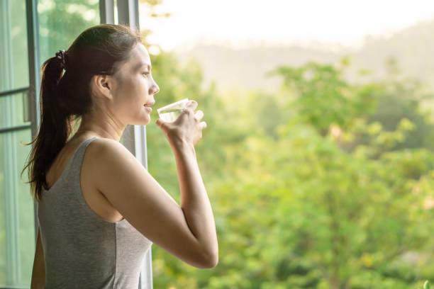 aziatische vrouw drinkt schoon water in de ochtend naast het raam met de natuur - woman water stockfoto's en -beelden