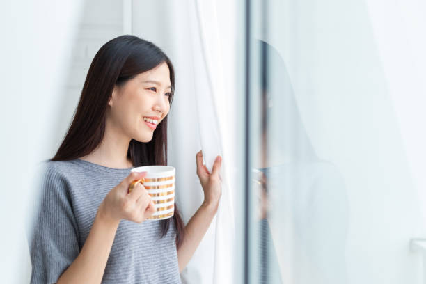 Asian woman drinking coffee in the morning after wake up stock photo