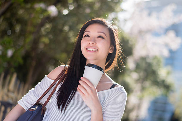 Asian woman drinking coffee on the go stock photo