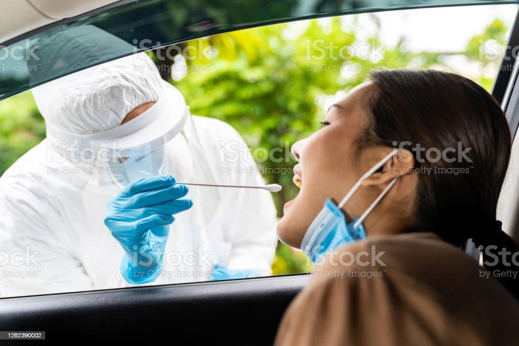 Aziatische vrouw Drive Thru covid-19 testen met PPE medisch personeel - Royalty-free Alleen volwassenen Stockfoto