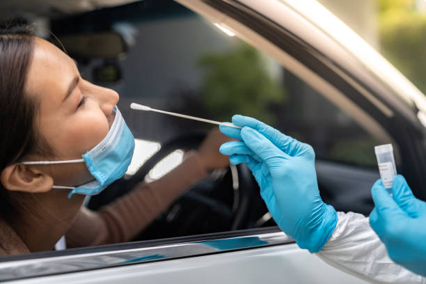 Asian woman Drive Thru COVID-19 testing with PPE medical staff stock photo