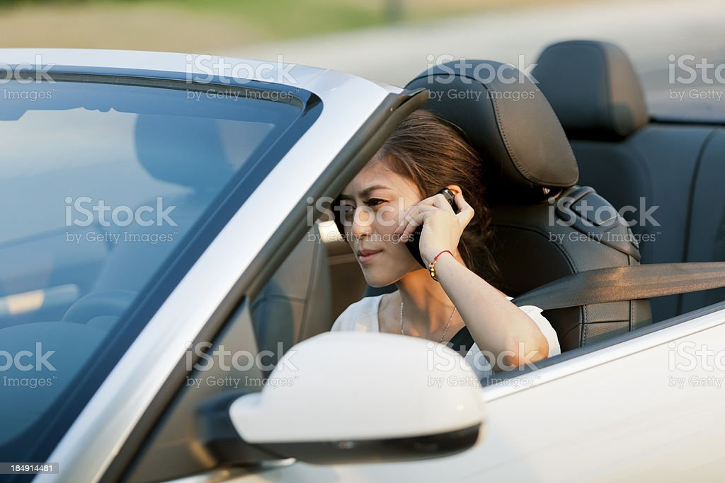 asian woman driving and talking on the cellphone stock photo