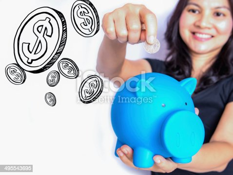 481974106istockphoto Asian woman dropping coin in piggy bank, thinking about  money 495543695