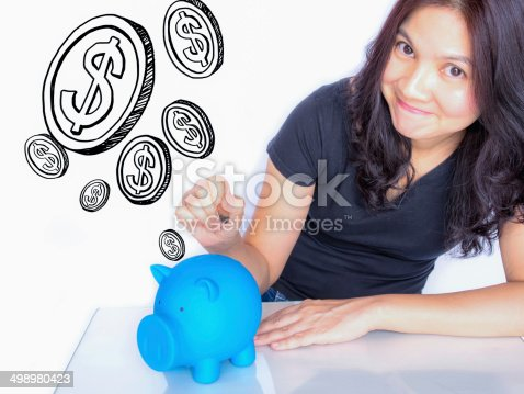 481974106istockphoto Asian woman dropping coin in piggy bank, thinking about  money 498980423