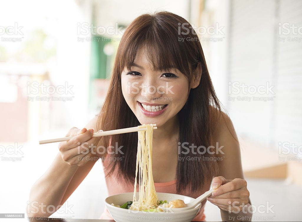 Asian woman eating noodles stock photo