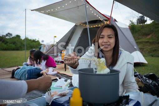 Asian woman eating shabu noodle outside the tent while camping with friend and family in the camping site with happiness. Family enjoy with nature and camping concept.