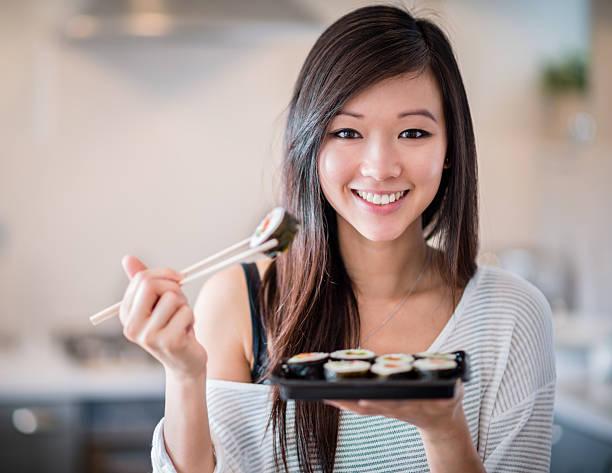 asiatische frau essen sushi - sushi essen stock-fotos und bilder