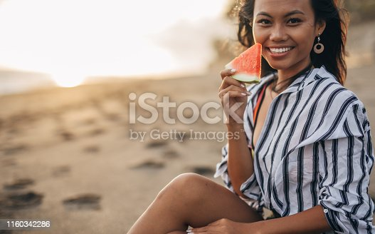 istock Asian woman eating watermelon 1160342286