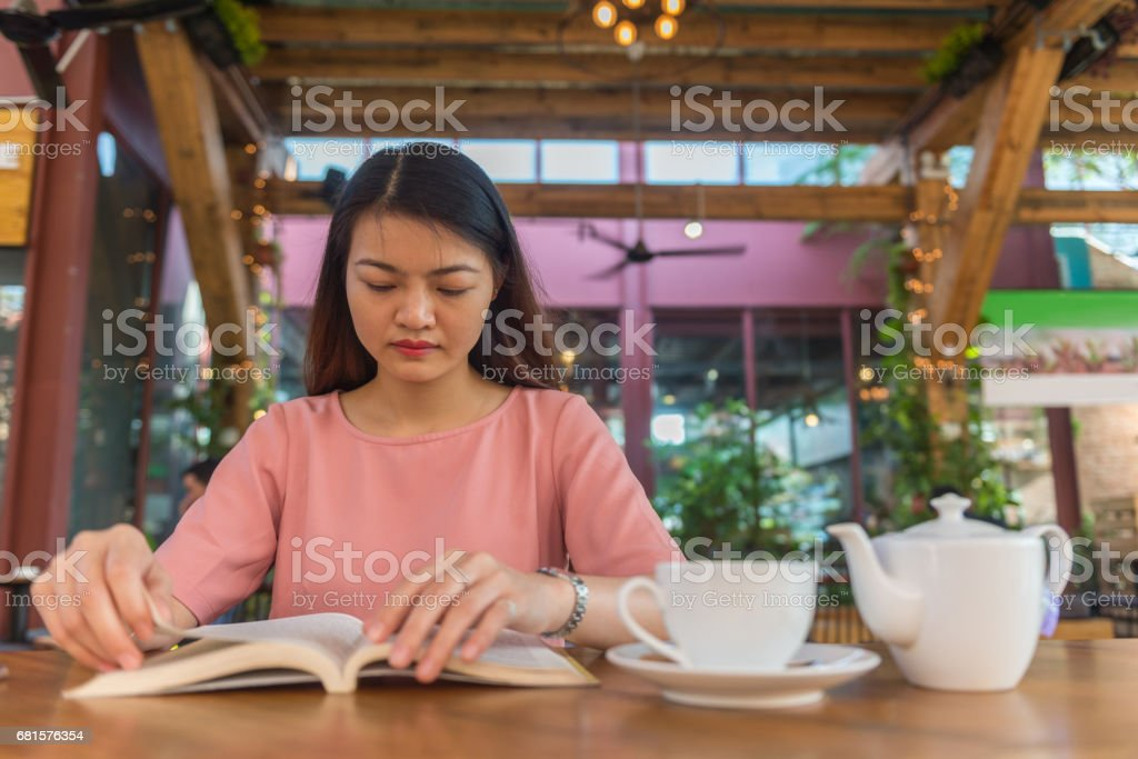 Asian woman enjoy her weekend, reading book and drinking hot tea stock photo