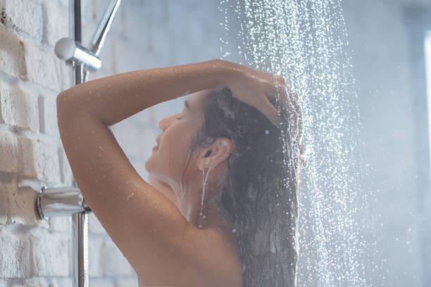 Asian woman Enjoying the shower She is washing her hair. stock photo