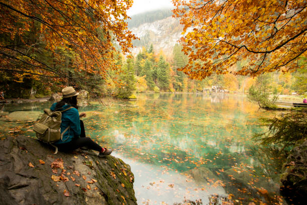 Asian woman  enjoying the view of turquoise lake Blausee in Swiss Alps stock photo