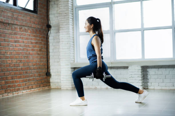 Asian woman exercise indoors she acted the leg lunge stock photo