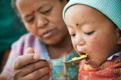 Outdoor image at day time of Asian woman feeding food to her grandson. The little child is opening his mouth wide to eat his lunch fed by his grandmother. Two people, Head and shoulders, horizontal composition and selective focus.