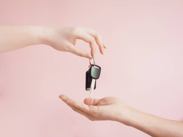 asian woman give her  car key to new car owner by beauty finger and hand with pink pastel background asian woman give her  car key to new car owner by beauty finger and hand with pink pastel background car key stock pictures, royalty-free photos & images
