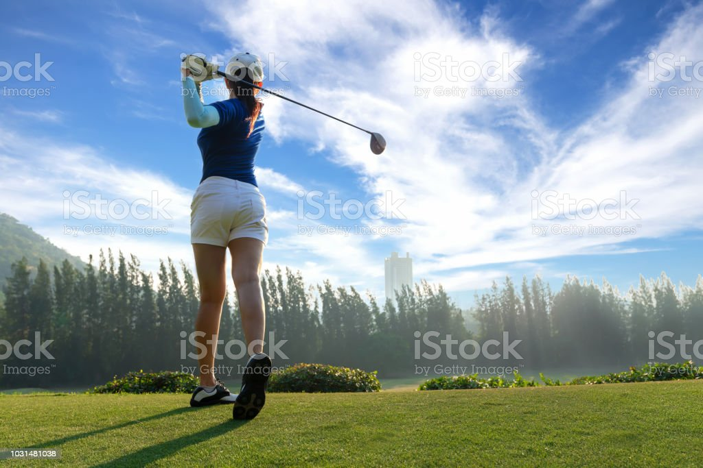 Asian woman golf player doing golf swing tee off on the green evening...
