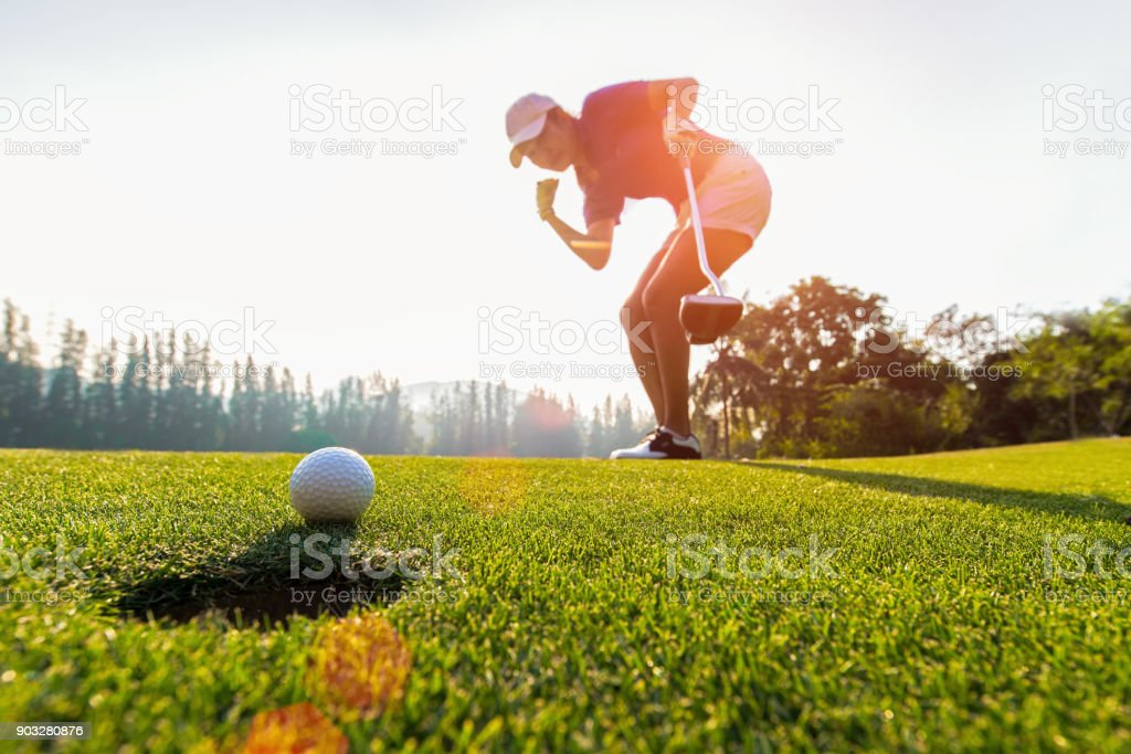 Asian woman golfer action to win after long putting golf ball on the green golf, sunset time, copy space.  Healthy Concept stock photo