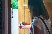 Asian woman grabbing knob opening wooden door