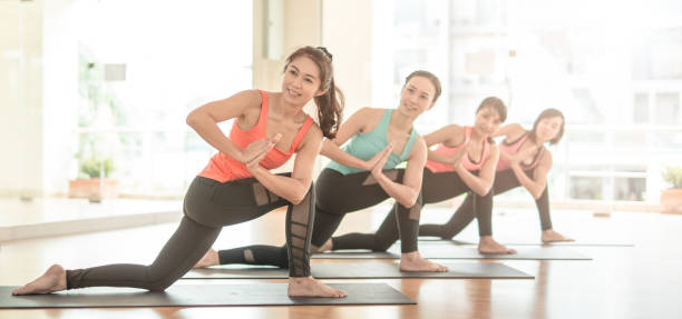 Asian woman group exercising do yoga in yoga classes stock photo