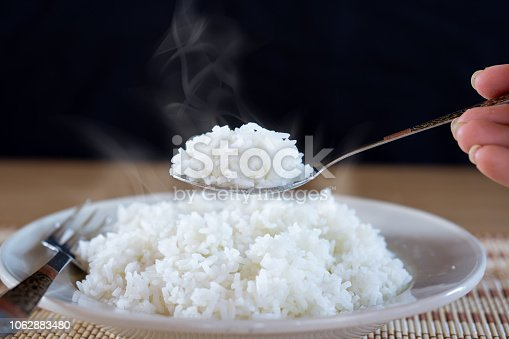 Asian woman hand eating cooked hot rice by spoon in a white plate
