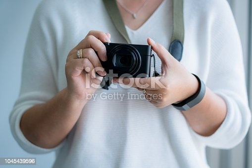 istock asian woman hand hold mirrorless camera 1045439596