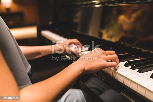 istock Asian woman hand playing keyboard of a piano in romantic atmosphere. Music instrument, solo pianist, song composer, hobby, practice study, or wedding event concept 930582530