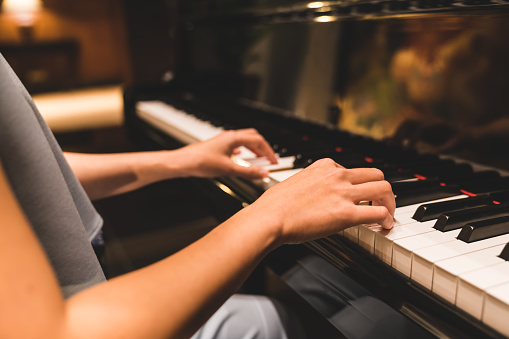 Asian woman hand playing keyboard of a piano in romantic atmosphere. Music instrument, solo pianist, song composer, hobby, practice study, or wedding event concept