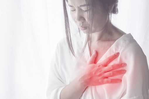 istock Asian woman hand touching her chest having heart attack 876497384