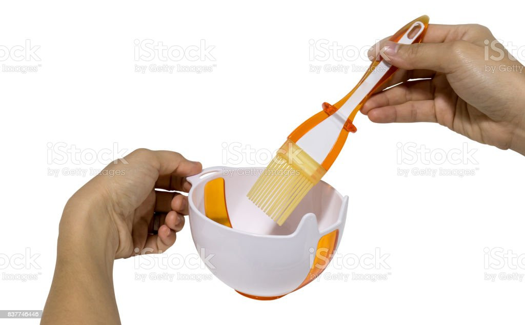 Asian woman hands holding a set of silicone baking brush and kitchen oil cup stock photo