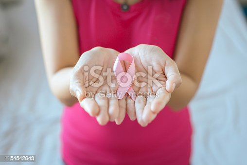 istock Asian woman hands holding pink ribbon,Breast cancer awareness concept,Close up 1154542643