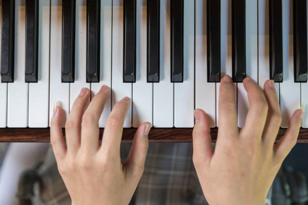 Asian Woman hands playing the piano in top view Asian Woman hands playing the piano in top view pianist stock pictures, royalty-free photos & images