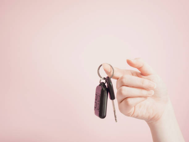 asian woman hanging car key by beauty right hand with pink pastel background asian woman hanging car key by beauty right hand with pink pastel background car key stock pictures, royalty-free photos & images