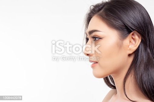 Asian woman has beautiful nose and nice face skin. Pretty girl show left hand side face. Attractive beautiful young woman looks at copy space. She has long hair. Glamour lady get natural makeup