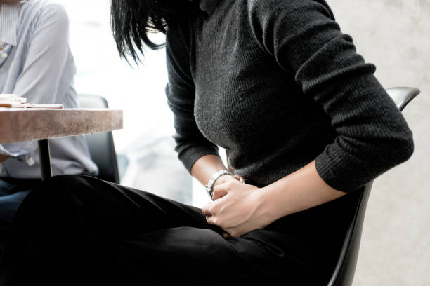 Asian woman has stomachache while she meeting with her friend in cafe. stock photo