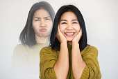istock Asian woman having double personality ,mood swings or bipolar disorder with different emotions 1296690622