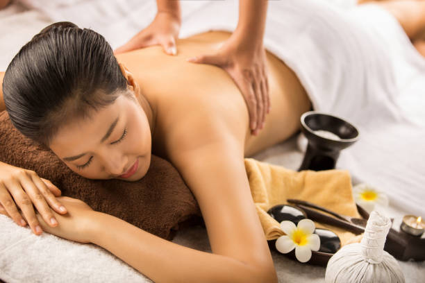 asian woman having massage and spa salon beauty treatment concept. she is very happy - thai massage stock photos and pictures