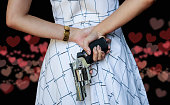 Young pretty Asian woman hiding a hand gun behind her back with both hands on heart bogeh background.