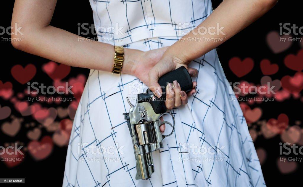 Asian woman hiding a hand gun behind her back. on heart stock photo