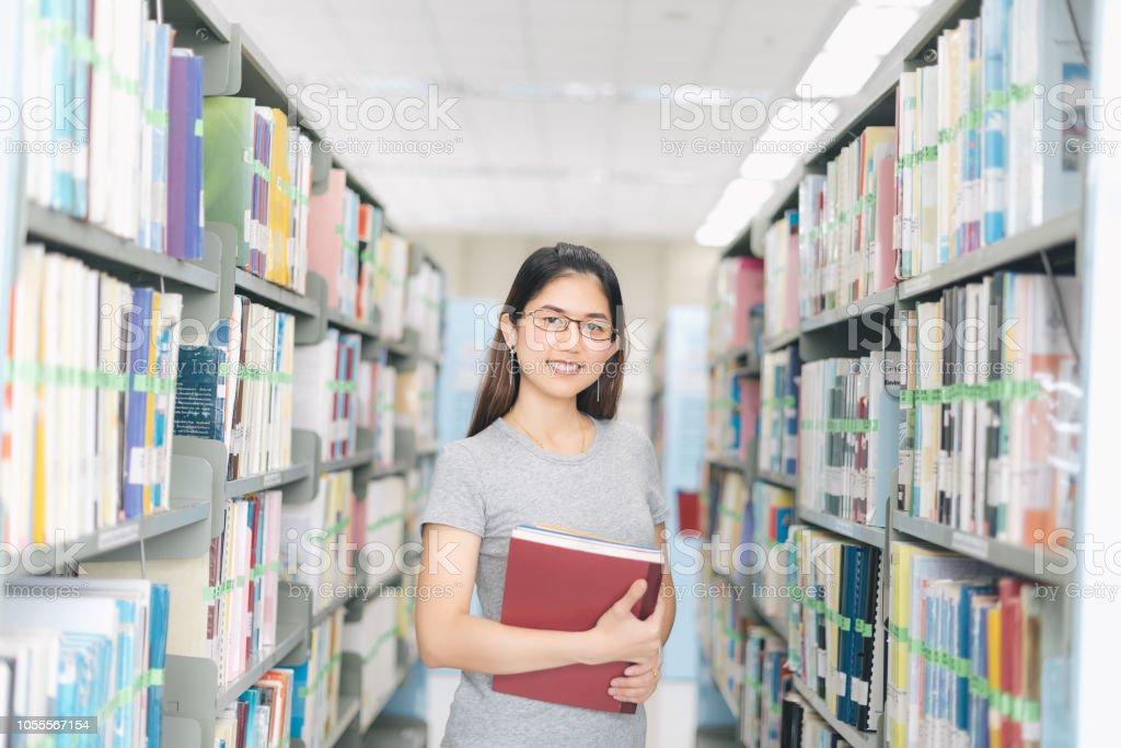 Asya bir kitap kitaplık kitaplığı'nda, tutan kadın.