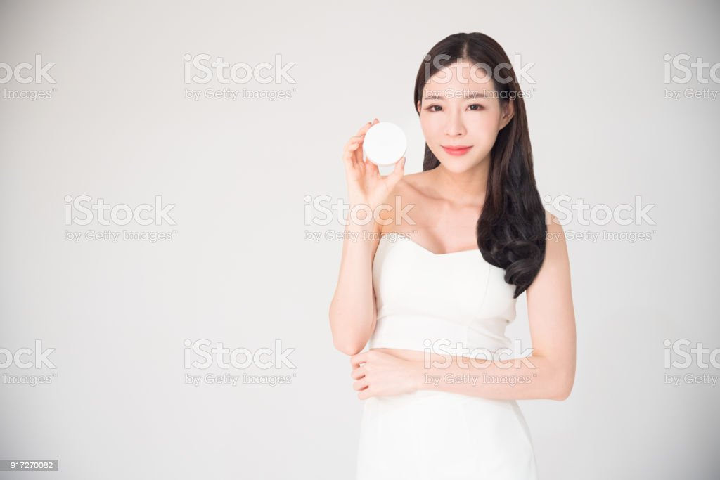 Asian woman holding cosmetics makeup product isolated on white background. Cosmetics product sale or promotion advertisement concept.