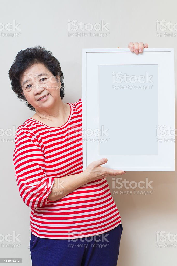 Asian woman holding empty white picture frame in studio shot, stock photo