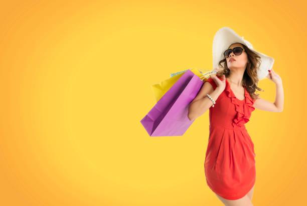 asiatische frau mit phantasie einkaufstaschen auf orangem hintergrund - kleider günstig kaufen stock-fotos und bilder
